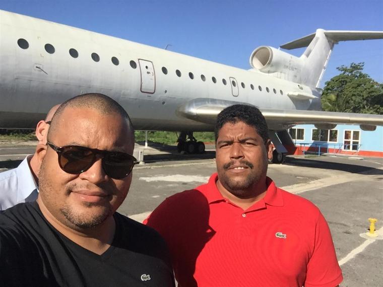 Selfie de Michel Mirabal y de fondo el avión que pintará próximamente